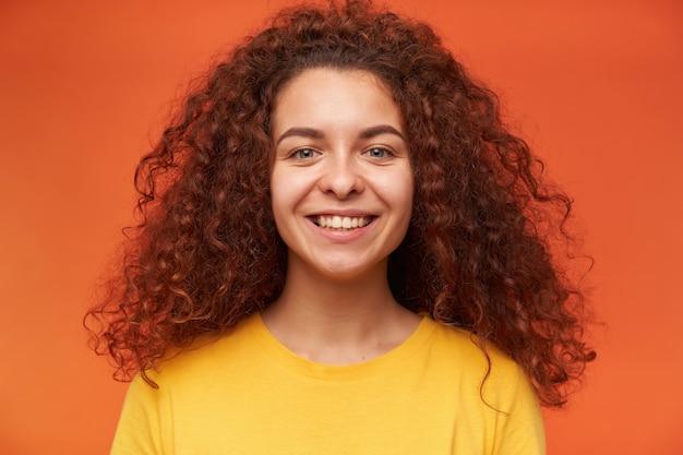 Tiener, gelukkig uitziende vrouw met gember krullend haar gele t-shirt dragen
