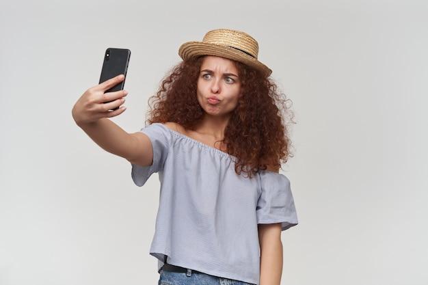 Tiener, gelukkig uitziende vrouw met gember krullend haar. gestreepte blouse en hoed met blote schouders. een selfie maken op een smartphone en pruilende lippen. tribune geïsoleerd over witte muur
