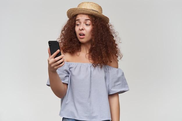 Tiener, gelukkig uitziende vrouw met gember krullend haar. gestreepte blouse en hoed met blote schouders. vasthouden en kijken naar haar smartphone, ongelukkig gezicht. tribune geïsoleerd over witte muur