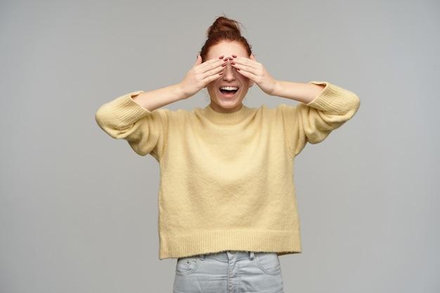 Tiener, gelukkig uitziende vrouw met gemberhaar verzameld in een broodje. pastelkleurige gele trui en spijkerbroek aan. bedek haar ogen met handpalmen en breed lachend. stand geïsoleerd over grijze muur