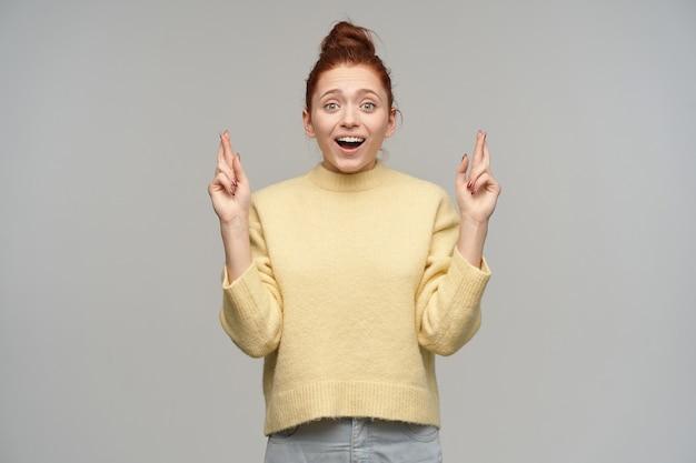 Tiener, gelukkig uitziende vrouw met gemberhaar verzameld in een broodje. pastelkleurige gele trui en spijkerbroek aan. kruis vingers, doe een wens. kijken opgewonden geïsoleerd over grijze muur