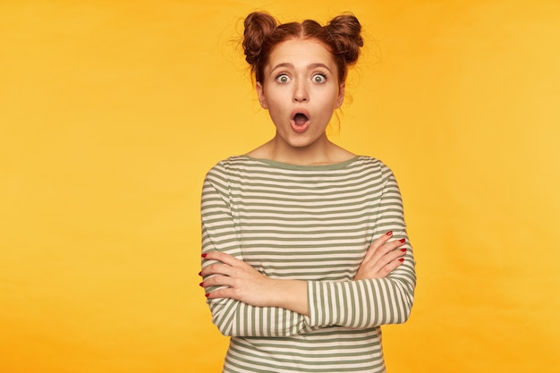 Tiener, geschokt uitziende vrouw met rood haar met twee broodjes. een gestreepte trui dragen en kijken met gekruiste handen op een borst en verbaasd gezicht. sta geïsoleerd over gele muur