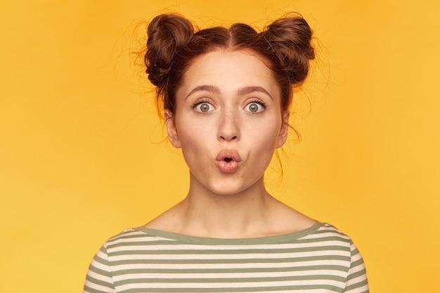 Tiener, geschokt uitziende vrouw met rood haar met twee broodjes. probeer de kaarsen uit te blazen. gestreepte trui dragen en kijken geïsoleerd, close-up over gele muur