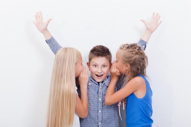 Tiener girsl die in de oren van een geheime tienerjongen fluistert op witte achtergrond