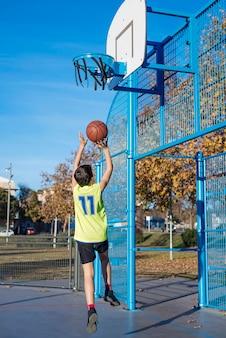 Tiener gooit een basketbal van achteren in de hoepel