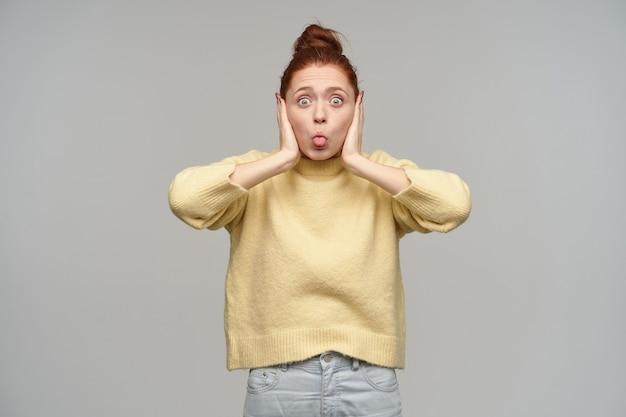 Tiener, grappig uitziende vrouw met gemberhaar verzameld in een broodje. pastelkleurige gele trui en spijkerbroek aan. bedek haar oren en laat de tong zien. geïsoleerd over grijze muur