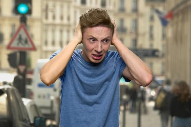 Tiener heeft een zenuwinzinking. huilende europese jongen sluit zijn oren met zijn handen. jonge jongen wil stilte. lawaaierige stad op de achtergrond.