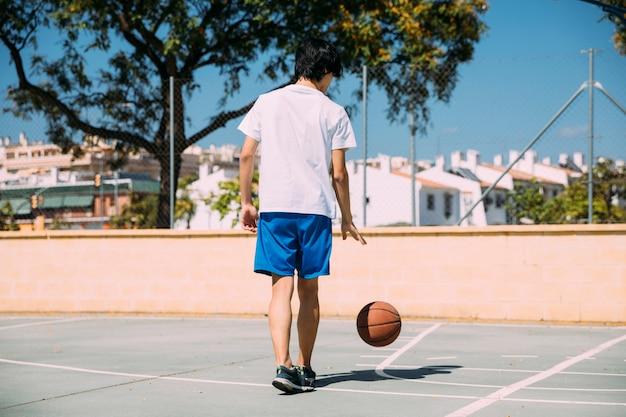 Tiener het spelen met bal bij hof