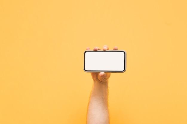 Tiener houdt een horizontaal gedraaide smartphone vast met een schoon wit scherm op geel