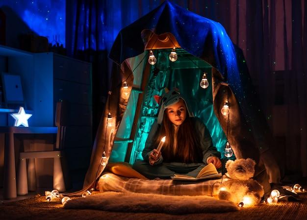 Tiener in de vorm van animezitting in de tent van het spelhuis. landschap met fantastische slingerverlichting