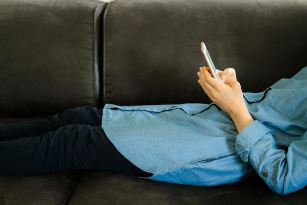 Tiener in een blauwe jurk die op een bank ligt terwijl ze een slimme telefoon vasthoudt