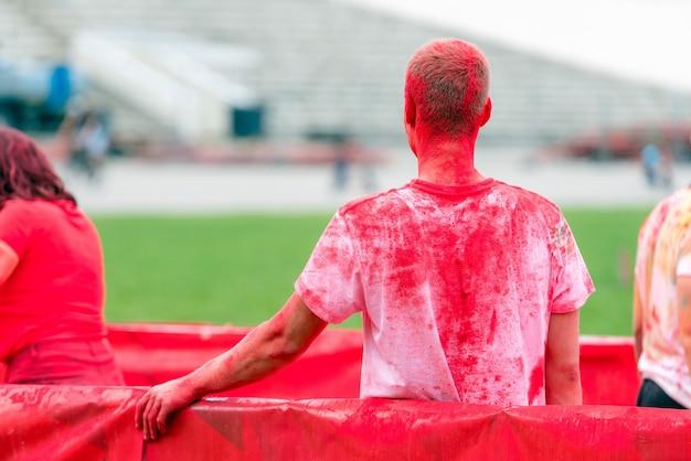 Tiener in een kleurenfestijn met rood stof op zijn t-shirt.
