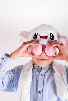 Tiener in een masker van easter bunny sluit zijn ogen met handgemaakte roze beschilderde eieren tegen lichtgrijze achtergrond.