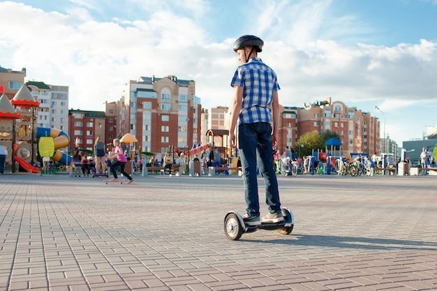 Tiener in een openbaar park rijden op een zelfbalancerende scooter in een beschermende helm.