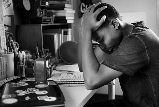 Tiener in een slaapkamer werkt gestrest en gefrustreerd