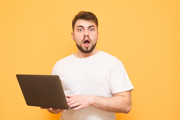 Tiener in een wit t-shirt met een laptop in zijn handen is geïsoleerd op geel