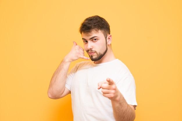 Tiener in een wit t-shirt toont een vinger geïsoleerd op geel