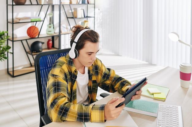Tiener in geruite overhemd hoofdtelefoon dragen bij het kijken naar muziekvideo op digitale tafel