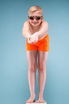 Tiener in oranje korte broek en zwemmende bril klaar om te springen