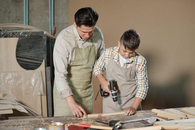 Tiener in schort met behulp van elektrische boor tijdens het maken van gat in houten plank onder controle van vader
