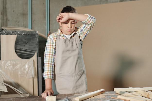 Tiener in schort moe na houtbewerking zweet afvegen van voorhoofd in werkplaats