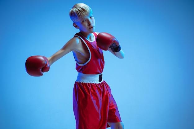 Tiener in sportkleding boksen geïsoleerd op blauwe studio achtergrond in neonlicht. beginnende mannelijke blanke bokser die hard traint en uitwerkt, schopt. sport, gezonde levensstijl, bewegingsconcept.