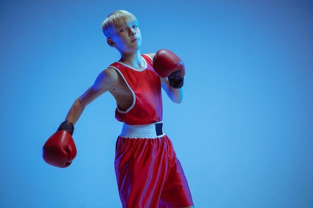 Tiener in sportkleding boksen geïsoleerd op blauwe studio wall Premium Foto