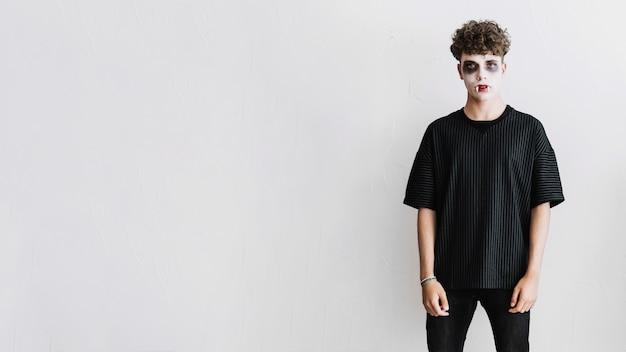 Tiener in zwarte kleding met vampier onverbiddelijke en hoektanden