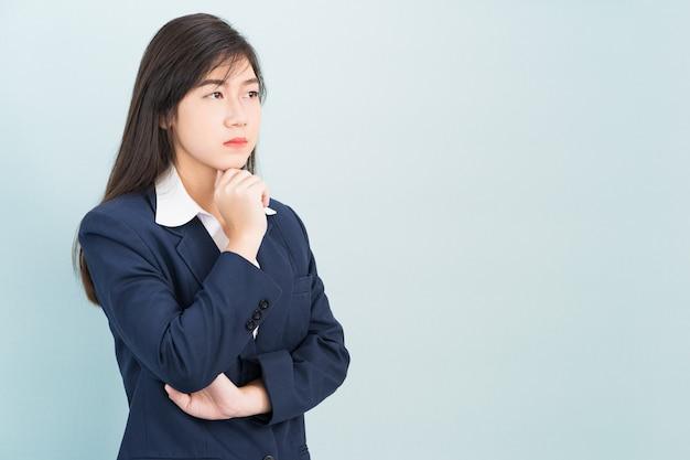 Tiener jong meisje gekleed pak met hand op kin geïsoleerd op blauwe achtergrond