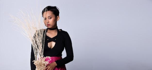 Tiener, jonge, aziatische vrouw, als, kort model, slijtage, zwart hemd, en, neon roze, kort rokje, gehouden, gedroogd, tak, boompje, met, neusring, studio, verlichting, grijze, achtergronden, geïsoleerde, kopie, ruimte