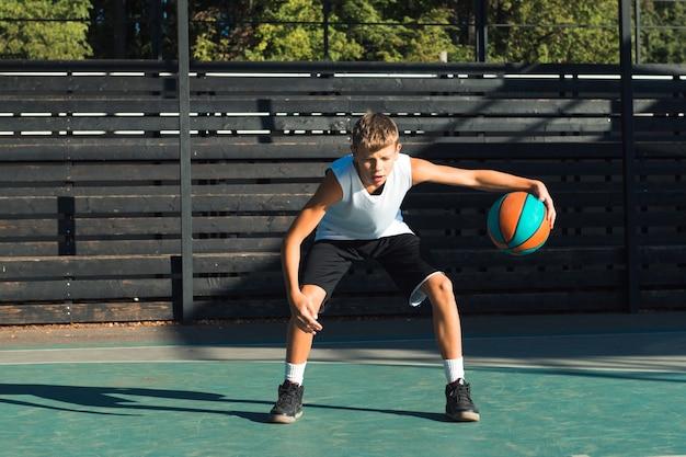 Tiener jongen basketbalspeler dribbelen op sportveld