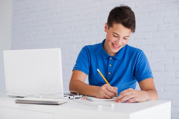 Tiener jongen huiswerk maken