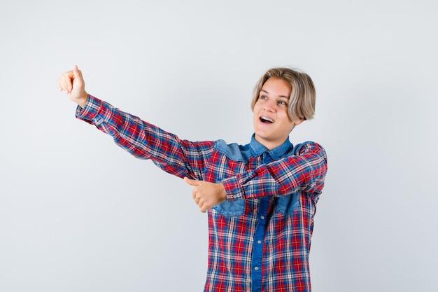 Tiener jongen in geruit hemd duimen opdagen en op zoek gelukkig, vooraanzicht.