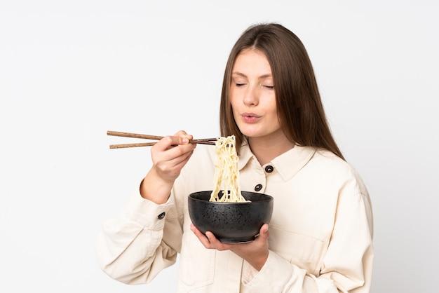 Tiener kaukasisch meisje dat op wit wordt geïsoleerd dat een kom noedels met eetstokjezand houdt die het blaast omdat zij heet zijn