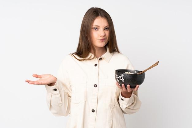 Tiener kaukasisch meisje dat op witte muur wordt geïsoleerd die twijfelsgebaar maakt terwijl het opheffen van de schouders terwijl het houden van een kom noedels met eetstokjes