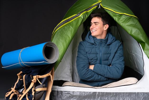 Tiener kaukasische mens binnen een het kamperen groene tent die op zwarte achtergrond in zijpositie wordt geïsoleerd