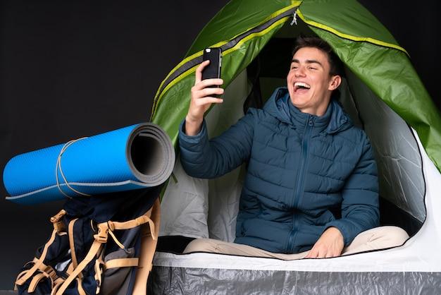 Tiener kaukasische mens binnen een het kamperen groene tent die op zwarte achtergrond wordt geïsoleerd die een selfie maken