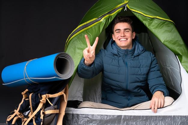 Tiener kaukasische mens binnen een het kamperen groene tent die op zwarte achtergrond wordt geïsoleerd die en overwinningsteken glimlacht toont