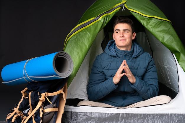 Tiener kaukasische mens binnen een het kamperen groene tent die op zwarte achtergrond wordt geïsoleerd die iets plannen