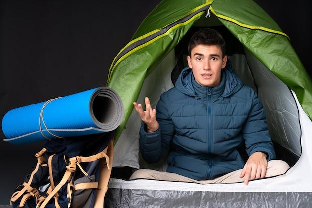 Tiener kaukasische mens binnen een het kamperen groene tent die op zwarte achtergrond wordt geïsoleerd die twijfelsgebaar maakt