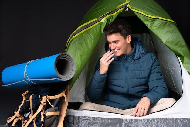 Tiener kaukasische mens binnen een het kamperen groene tent die op zwarte achtergrond wordt geïsoleerd die veel glimlacht