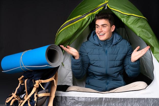 Tiener kaukasische mens binnen een het kamperen groene tent die op zwarte holding wordt geïsoleerd als achtergrond copyspace met twee handen