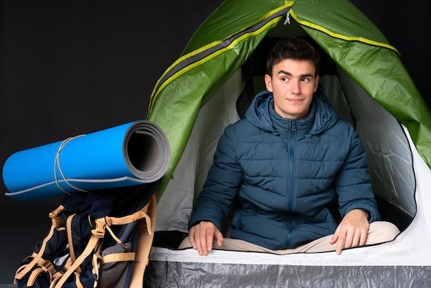 Tiener kaukasische mens binnen een het kamperen groene tent op zwarte muur die twijfelsgebaar maken die kant kijken