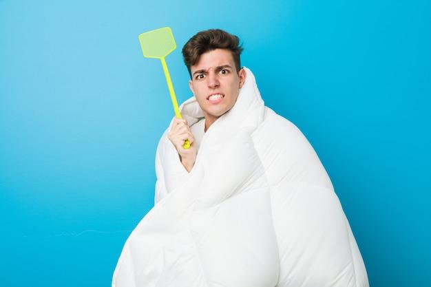 Tiener kaukasische vermoeide mens die zich met een deken behandelen en een vliegemepper houden