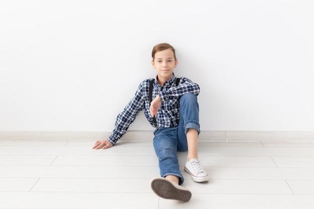Tiener, kinderen en manierconcept - portret van een manier knappe jongen op de witte achtergrond met exemplaarruimte