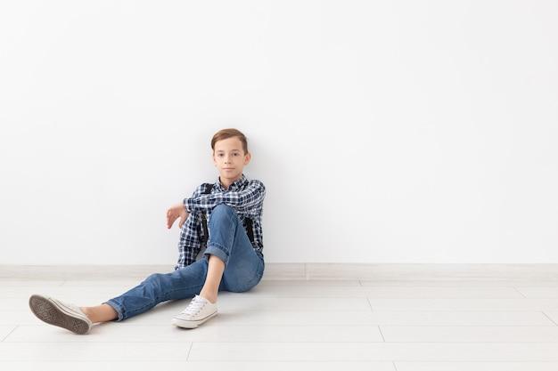 Tiener, kinderen en manierconcept - portret van een manier knappe jongen op de witte muur met exemplaarruimte