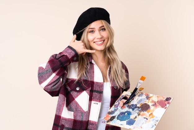 Tiener kunstenaar meisje met een palet geïsoleerd op blauw telefoongebaar maken en twijfelen