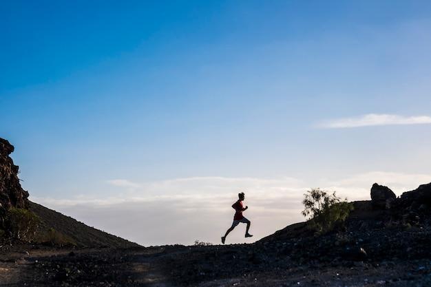 Tiener loopt alleen in de bergen met bergen op de achtergrond en prachtige zonsondergang - ftiness guy joggen geïsoleerd - zonnige dag en reis zonder stop