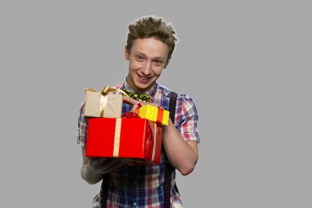 Tiener man met geschenkdozen camera kijken. gelukkige tiener met giftdozen tegen grijze achtergrond. winter vakantie vieren.