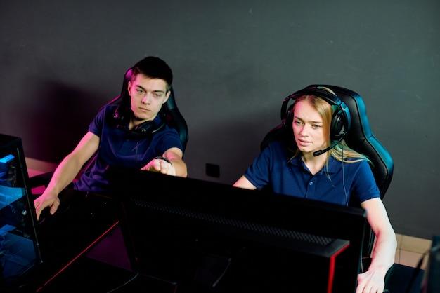 Tiener man wijzend op het scherm van de computer van zijn vriendin terwijl hij haar laat zien wat te doen om netwerkvideospel in club te winnen